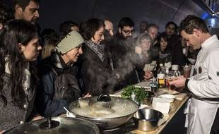 People wait to taste a dish  during the inauguration of the first edition of the International Taste Biennial (BIG - Internationale du Gout) on January 24, 2015 in the Croix Rousse tunnel in Lyon, central-eastern France, where a 1,7km buffet has been set up as part of the International Catering, Hotel and Food Show (SIRHA - Salon international de la restauration, de l'hÙtellerie et de l'alimentation). The International Taste Biennial runs from January 24 to 28, 2015.   AFP PHOTO / JEAN-PHILIPPE KSIAZEK