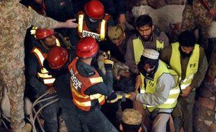 Des sauveteurs pakistanais portent une victime de  l'effondrement d'une usine dans la zone industrielle de Lahore, le 4 novembre 2015