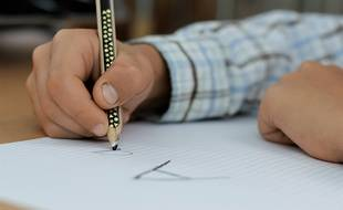 Un enfant en train d'écrire des lettres.