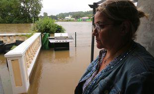 Une femme se tient devant sa maison inondée à Fismes, dans l'est de la France, le 15 juillet 2021, près des rives inondées de la rivière Ardre à la suite de fortes pluies tombées ces derniers jours.
