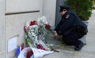 Une policière arrange des fleurs devant le consulat de France à New York, le 14 novembre 2015