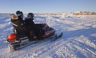 Deux personnes sur une motoneige au Canada (image d'illustration).