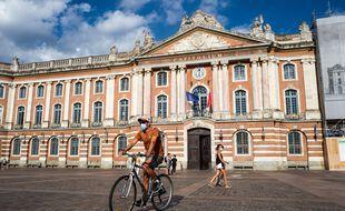 Un cycliste masqué dans le cadre de la lutte contre le coronavirus à Toulouse sur la place du Capitole.