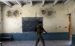 Un membre des forces de sécurité afghanes dans une école utilisée par Daesh dans le district de Kot, dans la province de  Nangarhâr, (est de l'Afghanistan)