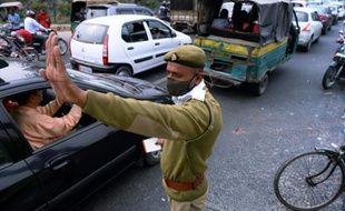 Un policier portant un masque dans la banlieue de New Dehli le 25 février 2015