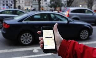Une personne utilise l'application Uber sur son smartphone (illustration).