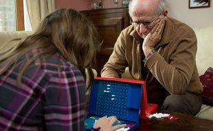 Un  monsieur et sa fille joue à un jeu de société.