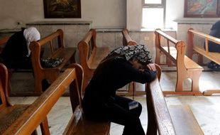 Des Assyriennes déplacées de leurs villages syriens par l'avancée des troupes du groupe EI, prient dans l'église grecque catholique melkite Ibrahim al Khalil dans la banlieue de Damas, le 1er mars 2015