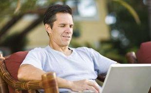 Un homme travaille sur son ordinateur portable.