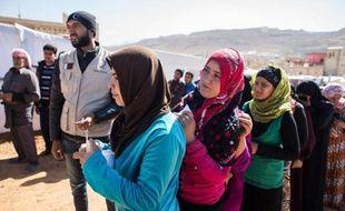 Des réfugiés syriens attendent une distribution de nourriture au camp d'Al-Masri, près de la ville libanaise d'Arsal, le 25 octobre 2014