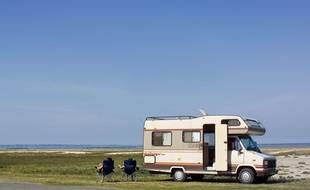 Illustration d'un camping-car garé près d'une plage en Bretagne.