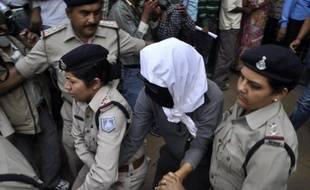 Une femme suisse (c), victime d'un viol collectif dans le centre de l'Inde, est escortée par des policiers jusqu'à l'hôpital de Gwalior, le 16 mars 2013