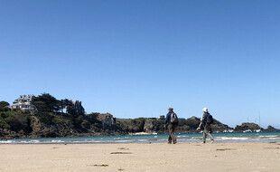 Un couple marche sur la grande plage de Saint-Lunaire, en Ille-et-Vilaine.