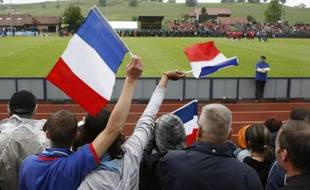 Swiss fans supporting the French team wave flags as the team enters the field for their frist  training session in Chatel St-Denis near Vevey, June 5, 2008. The French soccer team is preparing for the upcoming Euro 2008 Championship.  REUTERS/Charles Platiau (SWITZERLAND) (EURO 2008 PREVIEW)