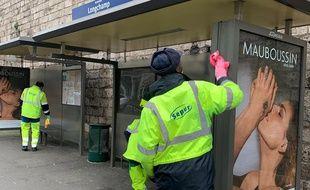 Des agents désinfectent un abribus à Suresnes, mardi 17 mars.