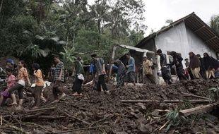 Les villageois marchent dans la zone touchée par des glissements de terrain à Java, en Indonésie. Dimanche 19 juin 2016.