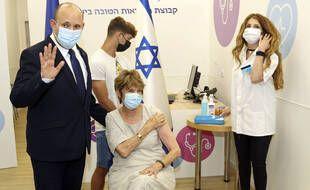 Le Premier ministre israélien, Naftali Bennett, avec sa mère qui s'apprête à recevoir une troisième dose de vaccin contre le Covid-19, à Haïfa le 3 août 2021.