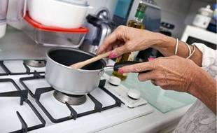 Une femme prépare à manger dans sa cuisine.