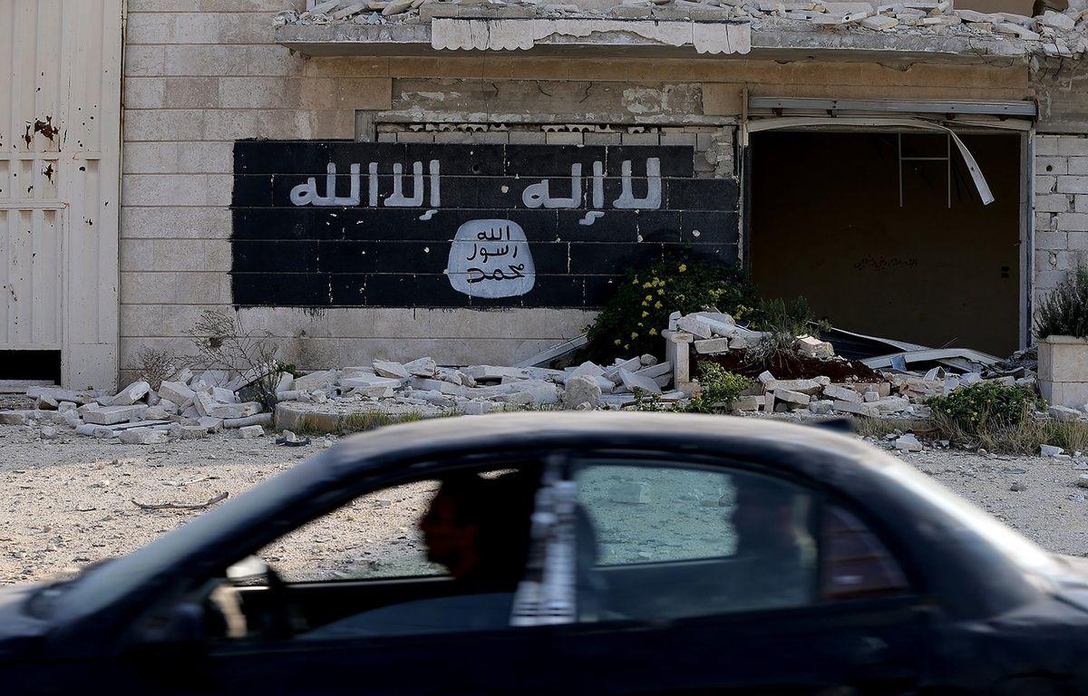 Des Syriens passent en voiture devant une usine détruite où a été peint le drapeau de Daesh, à Alep, le 18 novembre 2014. – JOSEPH EID / AFP