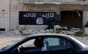 Des Syriens passent en voiture devant une usine détruite où a été peint le drapeau de Daesh, à Alep, le 18 novembre 2014.