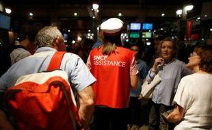 Un agent SCNF informe des passagers à la Gare du Nord, à Paris, après une suspension du trafic ferroviaire le 19 juillet 2016