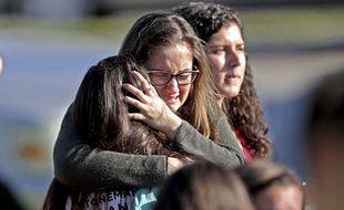 Une mère enlace sa fille après la fusillade qui a fait 17 morts dans un lycée de Parkland, en Floride, le 14 février 2018.