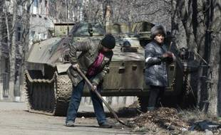 Des habitants de la ville de Debaltseve, dans l'est de l'Ukraine, nettoient leurs rues devant un char immobilisé, le 9 mars 2015