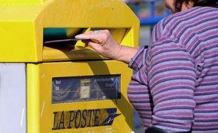 Une femme glisse une enveloppe dans une boite aux lettres, le 10 septembre 2013 à Lille (Photo illustration)