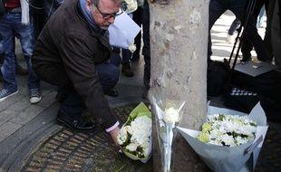 Paris, le 21 avril 2017. - Denis Jacob, secrétaire général du syndicat d'Alternative Police CFDT, dépose des fleurs à l'endroit où un policier a été tué par un assaillant sur les Champs-Elysées, la veille.
