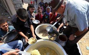 Des familles irakiennes yazidis mangent dans une école à Dohuk le 5 août 2014, après avoir fui la ville de Sinjar
