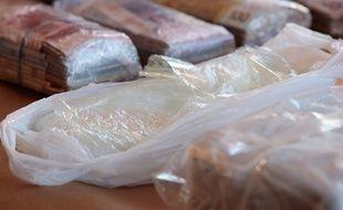 Photo d'illustration d'une saisie de cocaïne et de liasses de billets.