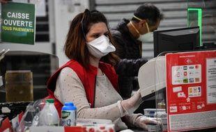 Illustration d'une employée d'un supermarché à la caisse, lors de l'épidémie de coronavirus