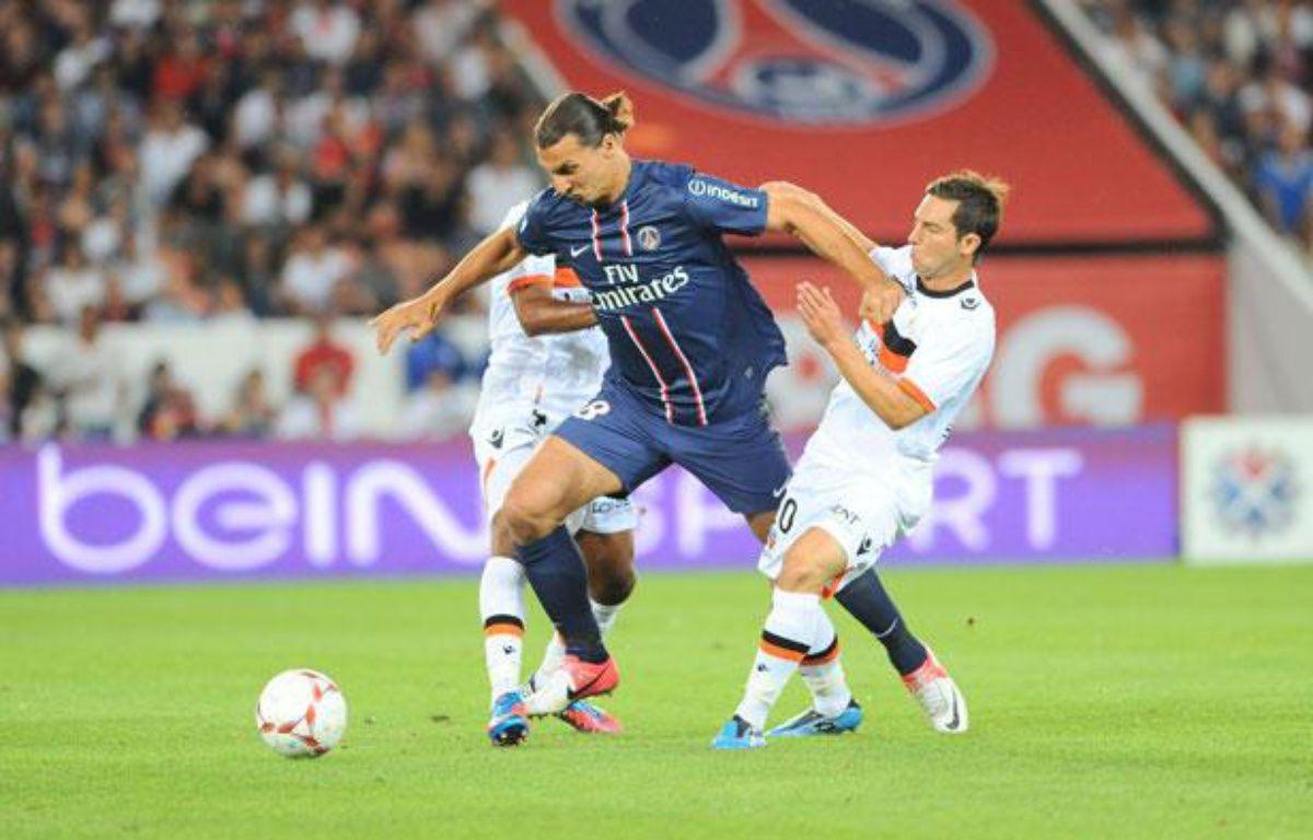 Zlatan Ibrahimovic s'infiltre entre deux joueurs lorientais, le 12 août 2012 au Parc des Princes.  – A.REAU/SIPA