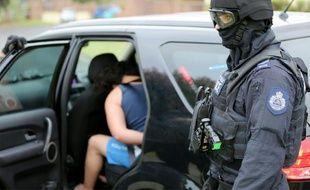 Cette photo, remise par la police de Nouvelle-Galles du Sud le 10 décembre 2015, montre un homme (g) qui se fait arrêter dans le cadre d'une enquête antiterrorisme à Sydney