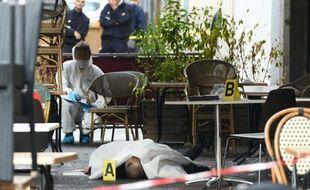 Des médecins légistes de la police recueillent des indices près du corps d'un homme tué dans une fusillade devant un bar, le 13 septembre 2015 à Marseille