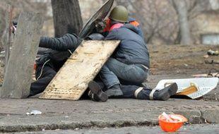 Des manifestants se protègent des tirs des snipers, rue Institutskaya, à Kiev, le 20 février 2014.