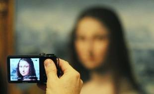 Un visiteur photographie une copie authentifiée de la Joconde de Léonard de Vinci présentée au musée du Prado à Madrid le 21 février 2012