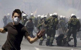 Un jeune manifestant s'enfuit alors que  d'autres sont frappés à coups de matraques par la police mercredi 11 mai  2011 à Athènes (Grèce). La police anti-émeute a utilisé beaucoup de gaz lacrymogènes pour  disperser les jeunes jetant des pierres.