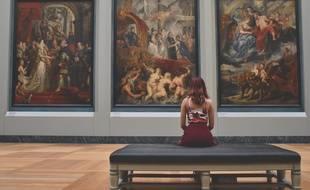 Illustration d'une personne admirant des œuvres d'art dans un musée.