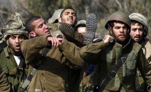 Des soldats israéliens portent un de leurs camarades, blessé dans une attaque du Hezbollah, le 28 janvier 2015 dans une zone occupée à la frontière du Liban
