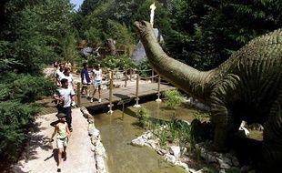 Des visiteurs regardent un brontosaure animé, le 11 juin 2003 à Dolancourt dans le parc Nigloland.