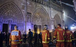 Des pompiers devant la façade de Notre-Dame dans la nuit du 15 au 16 avril 2019, alors que l'incendie qui a ravagé la cathédrale est sous «maîtrisé».