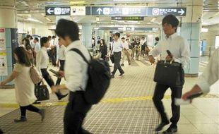 Les «salary men», qui se pressent dans le métro de Tokyo à l'heure de pointe, ont adopté les manches courtes.