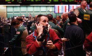 Un trader travaille avec trois téléphones à la bourse de New York, le 7 mars 2011.
