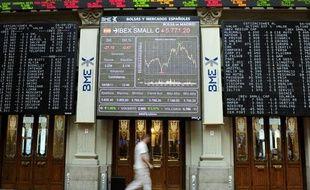 Un homme passe devant l'écran de la Bourse de madrid le 4 aout 2011