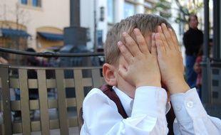 Un enfant qui se cache le visage avec ses mains. (illustration)