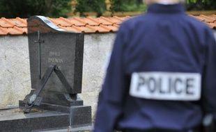 Policier devant une tombe dégradée le 4 août 2015 dans le cimetière de Labry