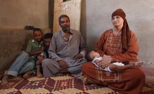 Une famille endettée aperçoit à peine la pyamide de Kheops de sa maison, cachée maintenant par un mur érigé en 2006, Égypte.