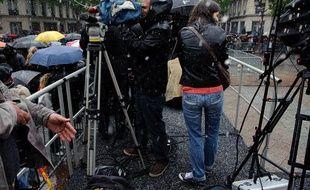Des journalistes sous la grêle devant l'Hôtel de Ville où François Hollande vient d'arriver, le 15 mai 2012.