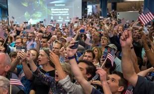 Drapeaux américains brandis pour saluer le succès de New Horizons le 14 juillet 2015 à Laurel, Maryland.